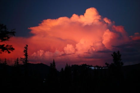 The cloud swells as the sun bathes it in orange and pink hues.